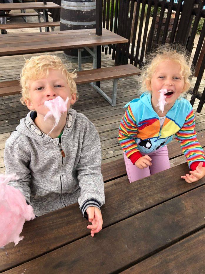 To børn spiser candyfloss. De har det udover hele hovedet og er glade.