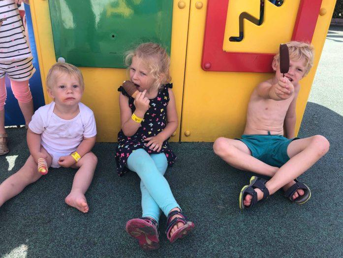 Tre børn sidder på en legeplads og spiser is. De har sommertøj på og sandaler.