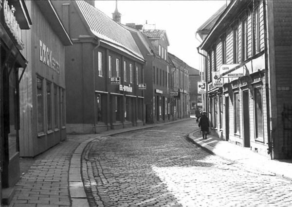 Köpmangatan i Eskilstuna 1973. Byggnaden som hyste El-Byrån var tidigare Adolf Fredriks hem. Huset härrör från 1700-tallet. Grannen med kvisten var stadens förstea apotek, byggt i senempirestil. Fotograf Lars Mårdbrandt.