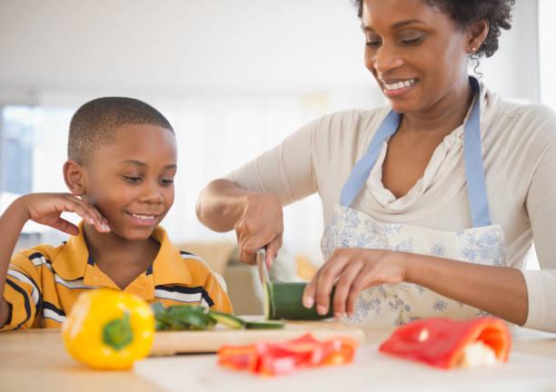 Une femme afro qui cuisine avec son fils.