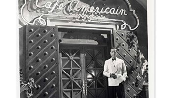 Humphrey Bogart as Rick, standing in front of Rick's Cafe Americain in Casablanca