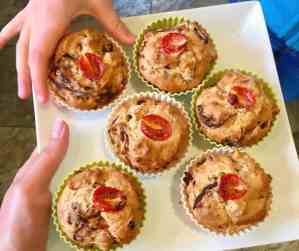 child taking vegan savoury muffin from a plate.