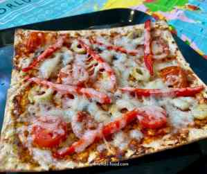 Matza pizza on a black plate.