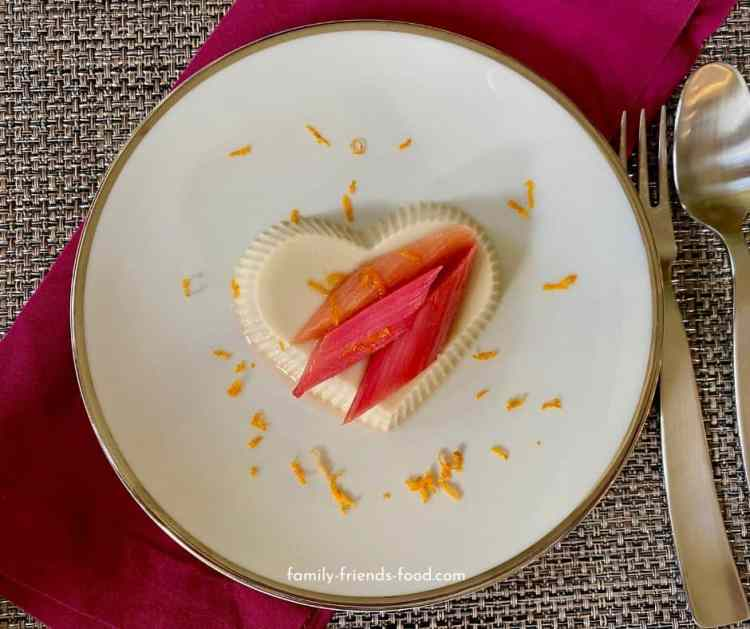 Vegan panna cotta with roasted rhubarb on white plate with fork and spoon.