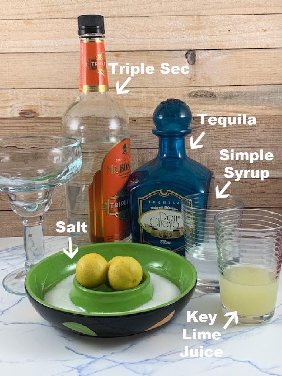 A photo with the ingredients necessary to make a Key lime margarita.