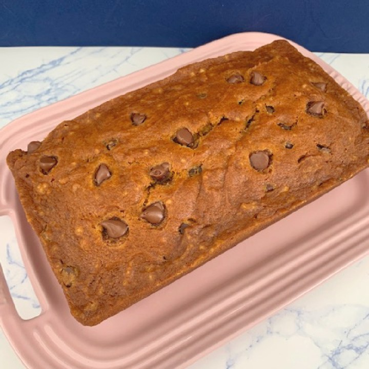 An uncut loaf of chocolate chip pumpkin bread on a platter.