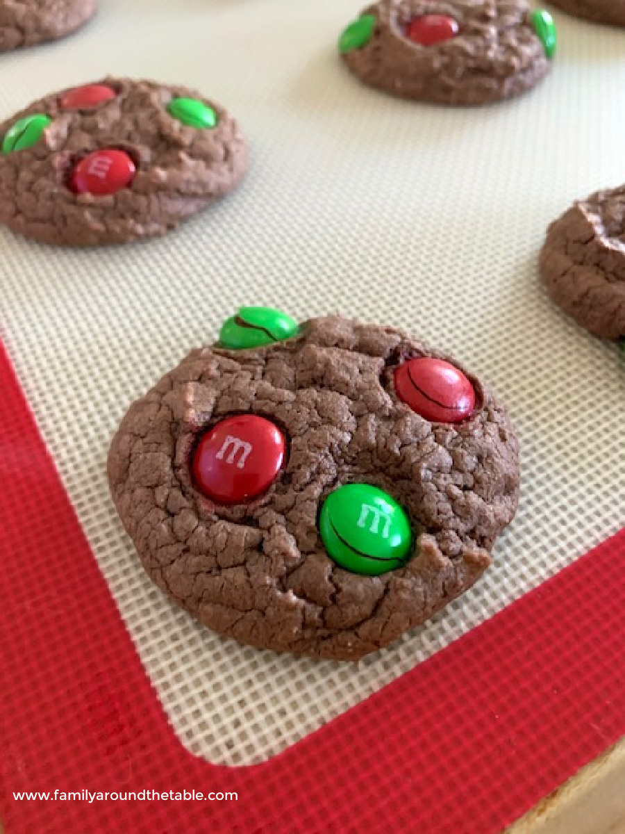Chocolate cookies sprinkled with M&M on a baking sheet warm from the oven.