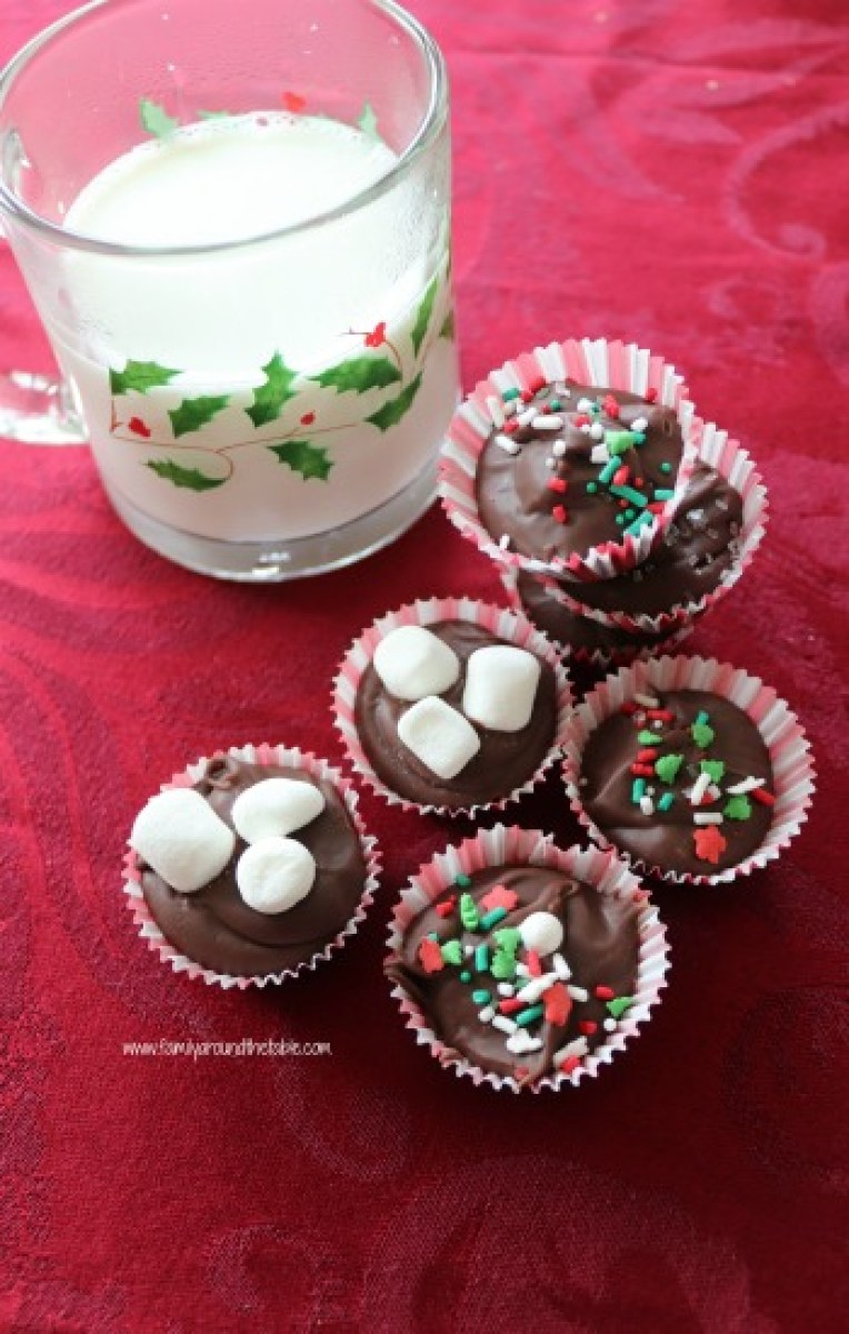 Hazelnut hot chocolate drops on a red tablecloth next to a mug of milk.