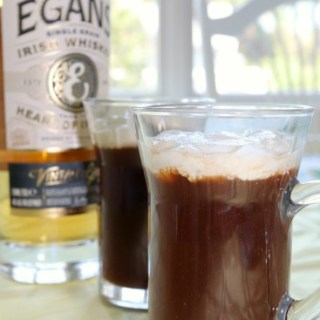 2 mugs of Irish coffee with a bottle of Irish Whiskey in the background.