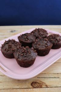 6 double chocolate banana muffins on a pink platter.