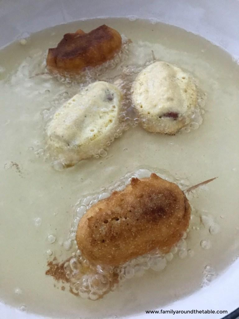 Mini corn dogs cooking in oil.