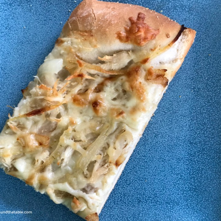 A slice of roasted garlic and chicken white pizza.
