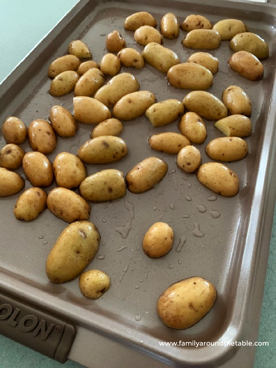 Potatoes on a sheet pan ready for the oven.