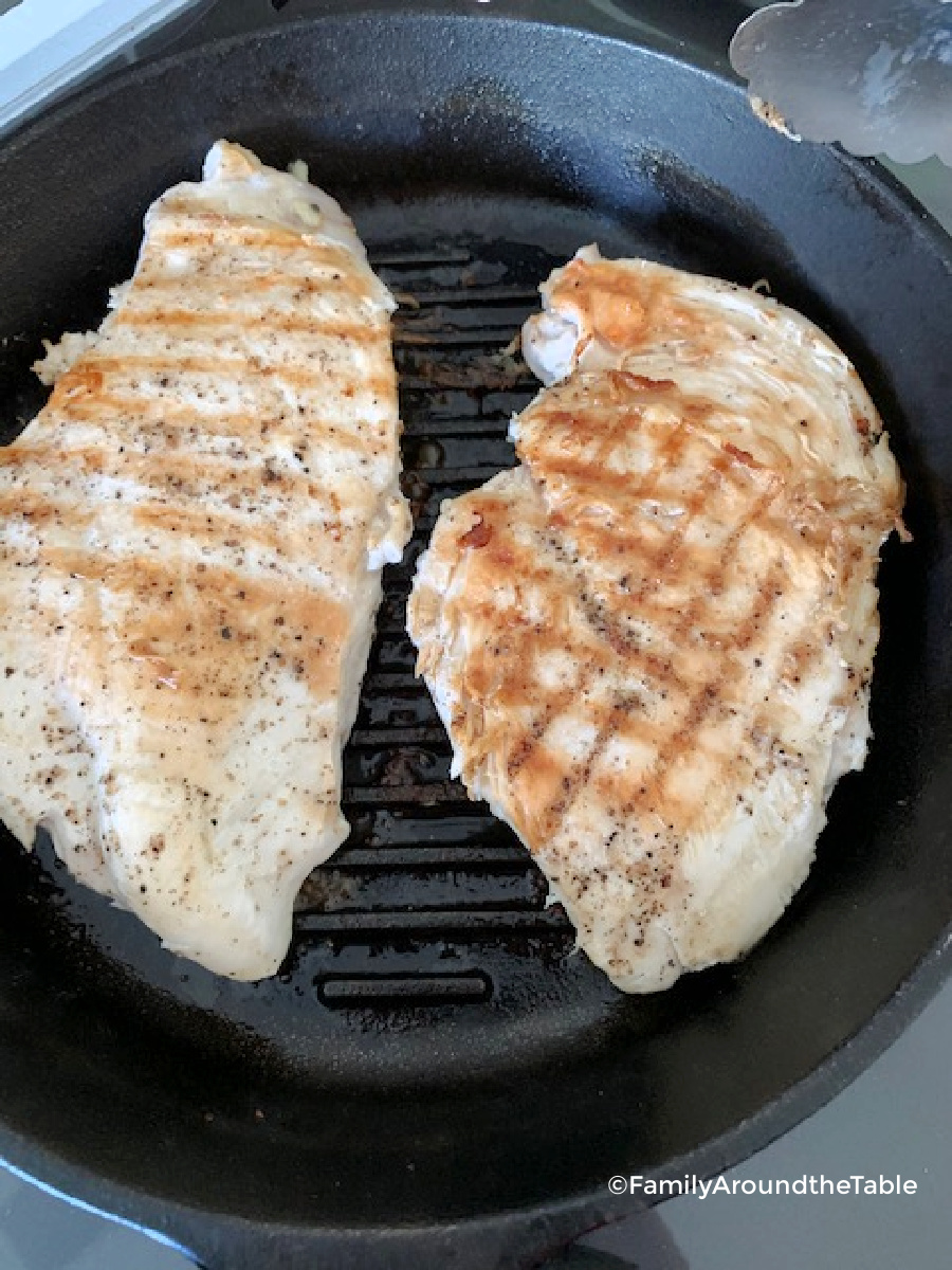 Two boneless skinless chicken breasts in a cast iron grill pan.