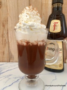 A clear mug of Frangelico hot chocolate with whipped cream and a bottle of Frangelico in the background.