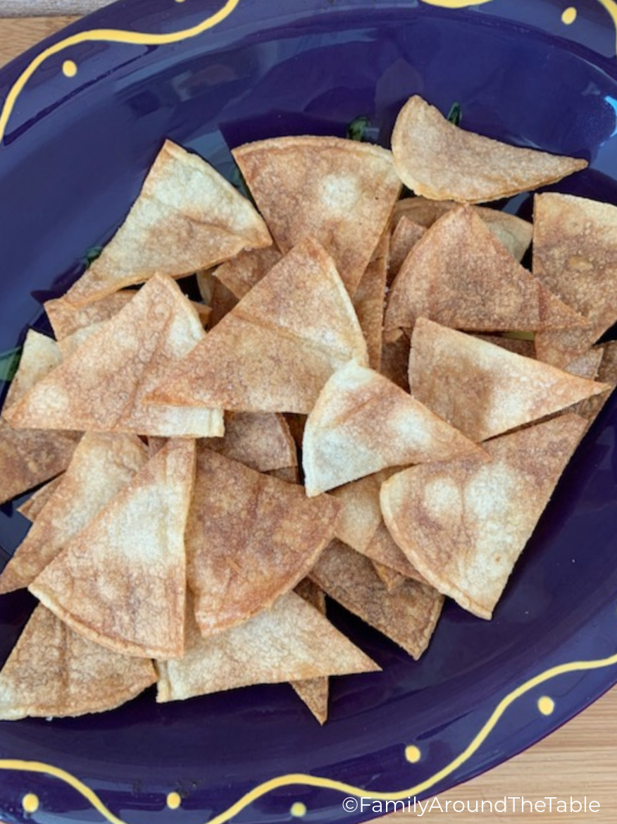 A pile of homemade tortilla chips in a purple bowl.