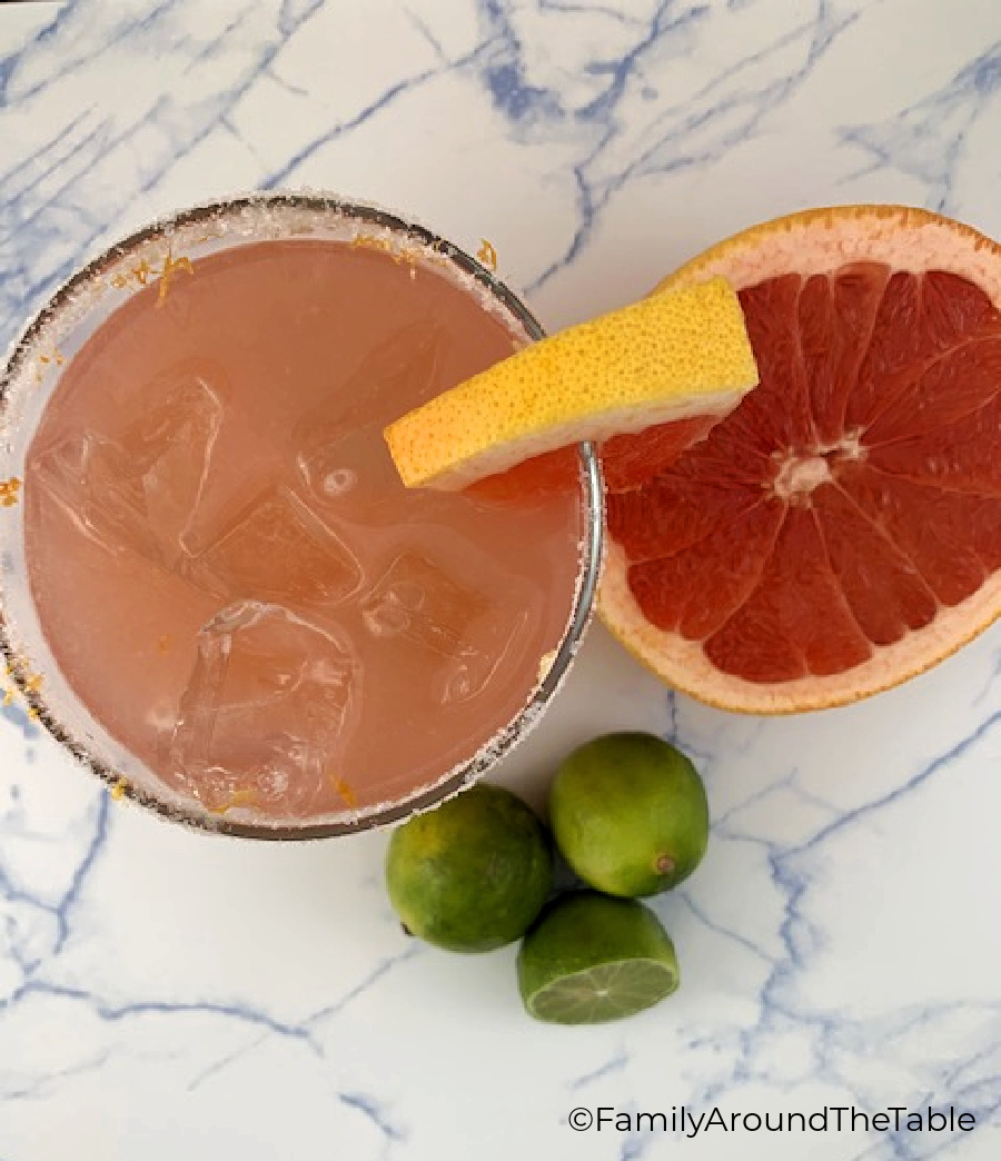 Overhead photo of a cocktail with limes and half a ruby red grapefruit.