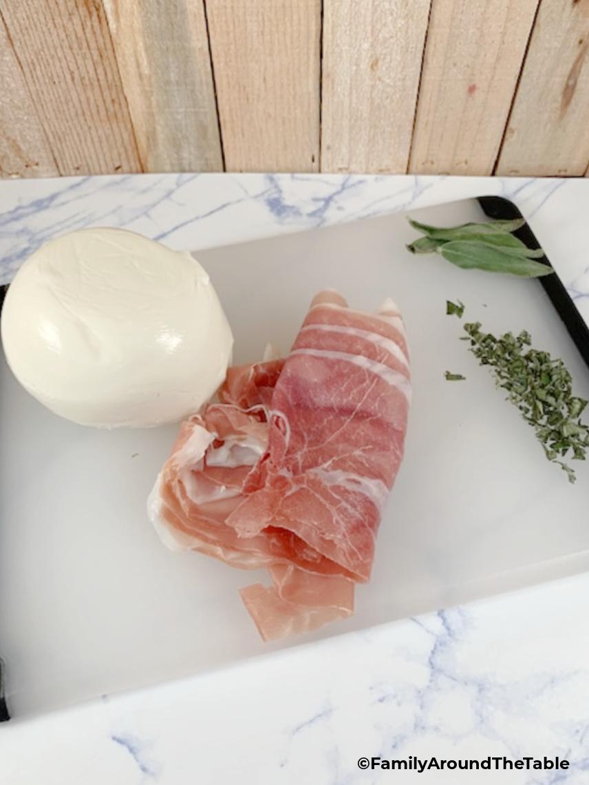 Mozzarella, prosciutto and chopped sage on a cutting board.