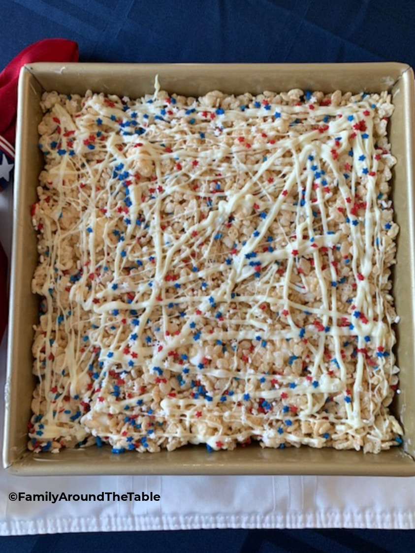 Overhead photo of Rice Krispie treats drizzled with white chocolate and patriotic sprinkles.