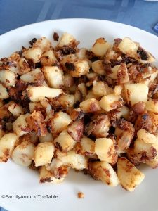 Cooked, cubed potatoes on a white plate.