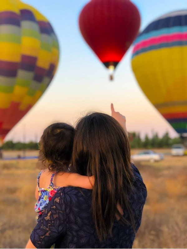 Single mother carrying daughter hot air balloons
