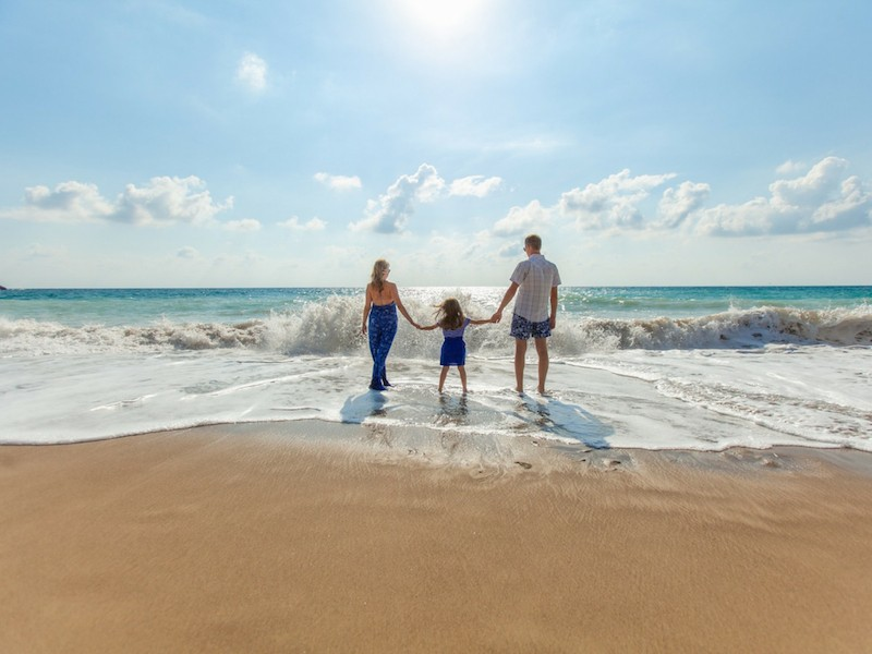 Blended family on beach with small waves