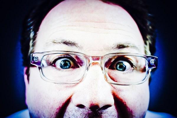 Webcam hacking man in glasses