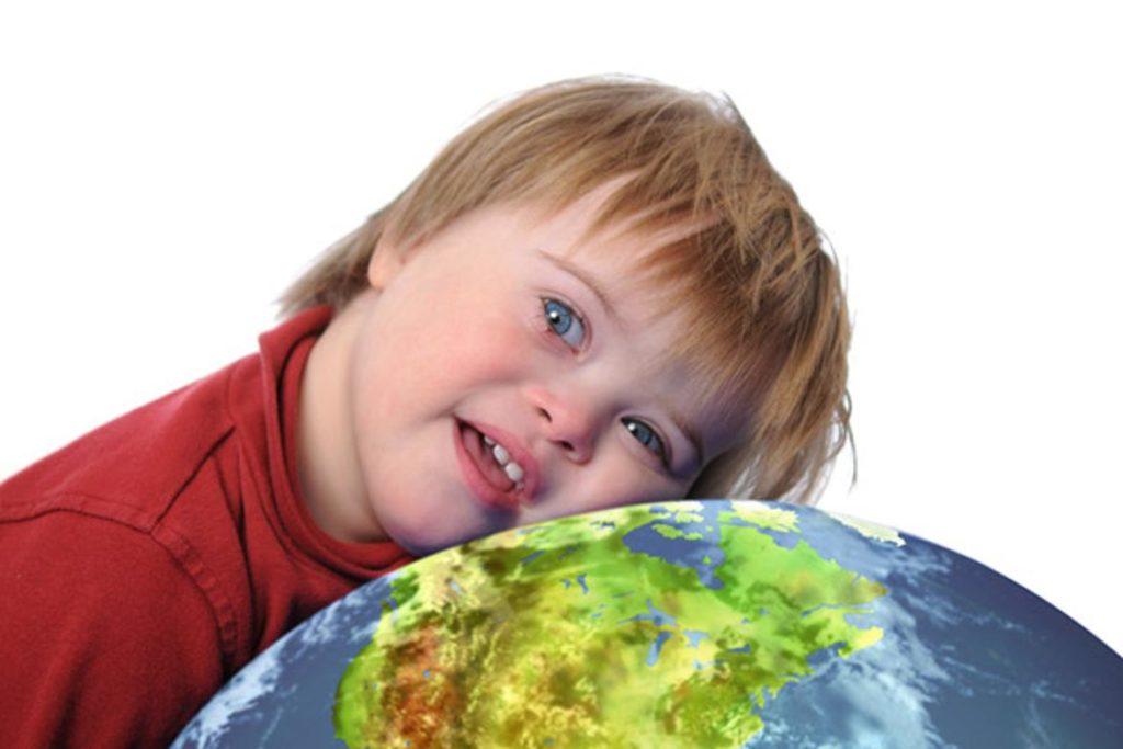 Niño con Sindrome de Down apoyado en el mundo