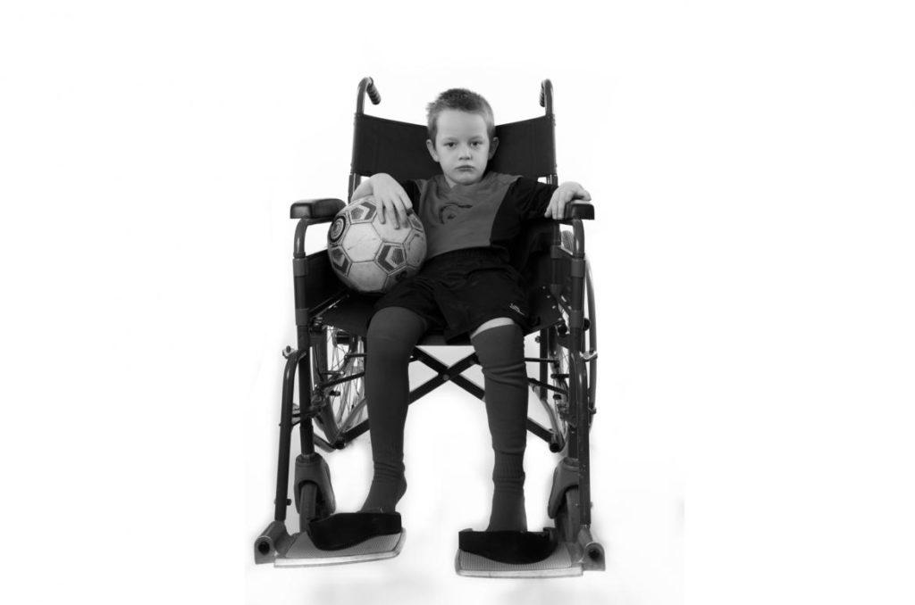 Niño en silla de ruedas de adulto