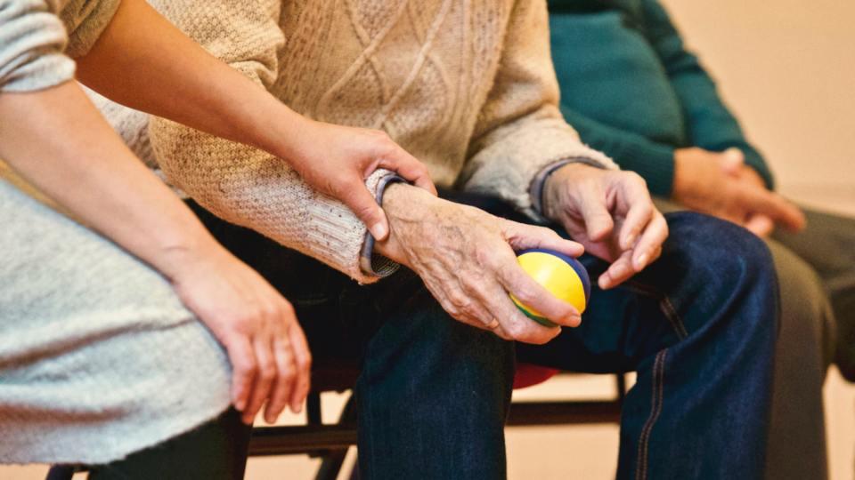 senior man in sweater holding stress ball
