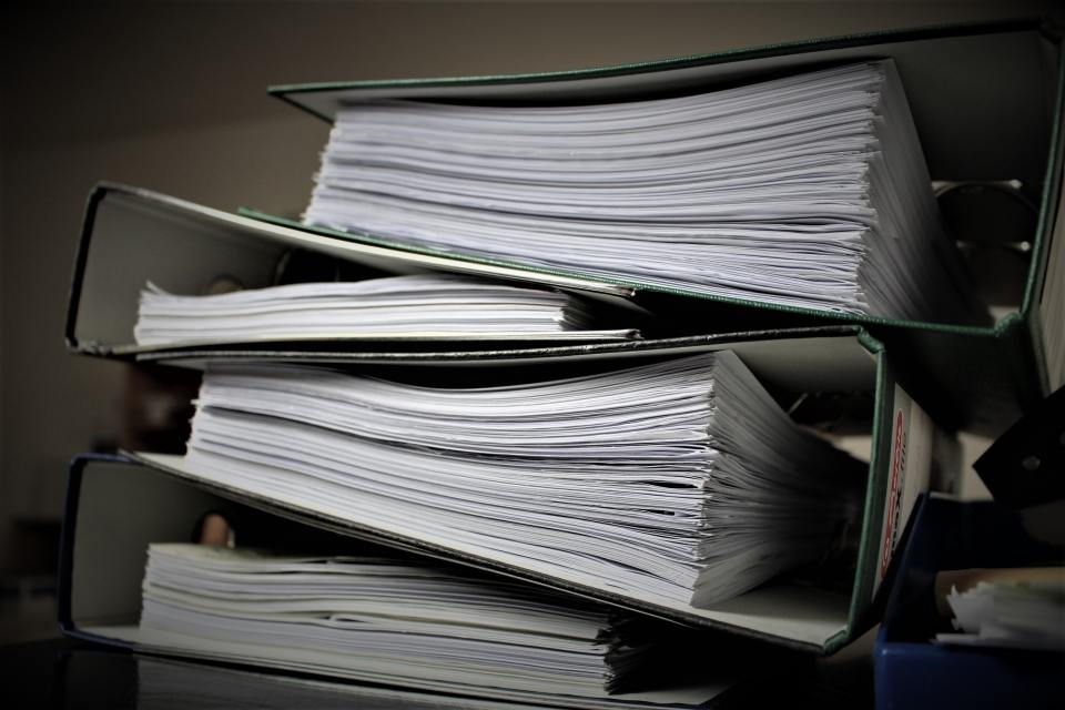 stack of large three-ring binders filled with paper