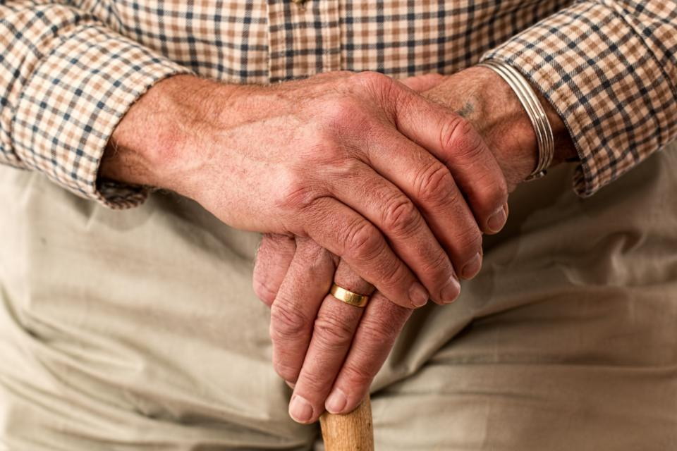 older man's hands holding a cane