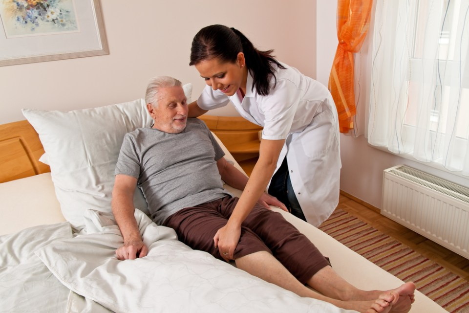 home care nurse helps elderly man out of bed.