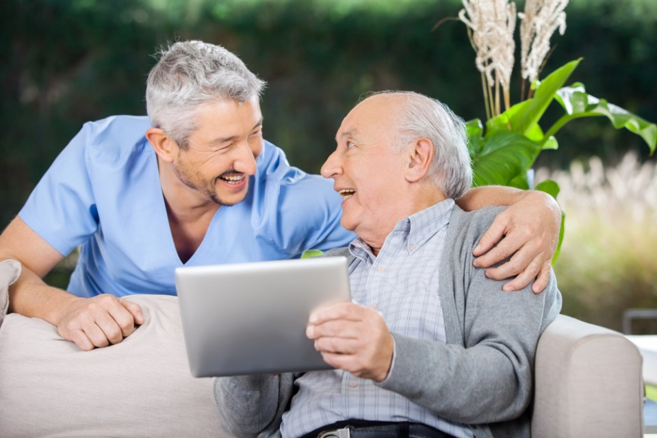 Laughing Caretaker And Senior Man Using Tablet Computer