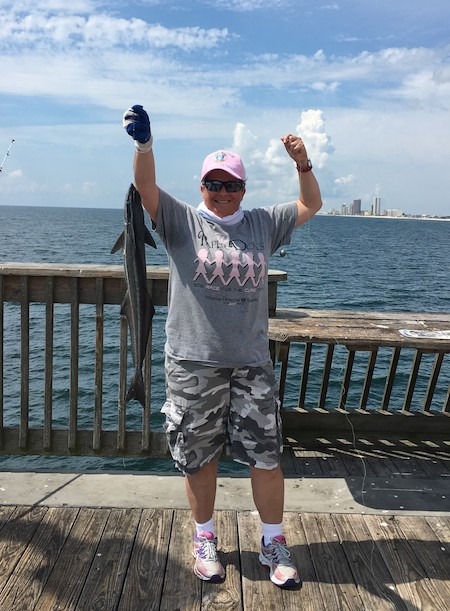 Lady from Arkansas catches her first fish ever at Gulf State Park Pier. She is very proud.