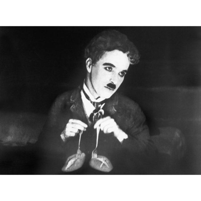Charlie Chaplin performing his classic dance of the dinner rolls