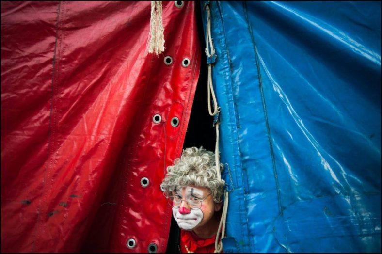 Barry Lubin as Grandma the Clown, peeking out from the circus tent