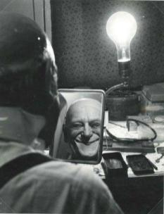 Grock applying makeup in a mirror