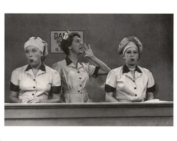 "An actual scene from the notorious ""Job Switching"" episode of I Love Lucy. Note how Lucy and Ethel's cheeks are bulging from the chocolates that they've been stuffing in their mouths, since the candy's been coming on the conveyor belt faster than they can deal with. Also note the forewoman's shouting to her coworkers to ""speed it up a little!"""