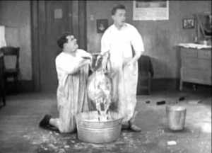 "Oliver Hardy and Stan Laurel washing Penelope the goat in ""Angora Love"""