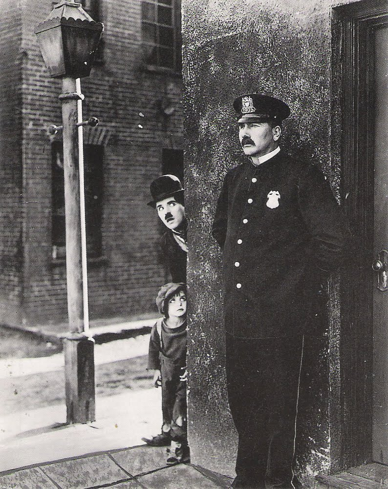 Jackie Coogan and Charlie Chaplin looking at a police officer around a corner