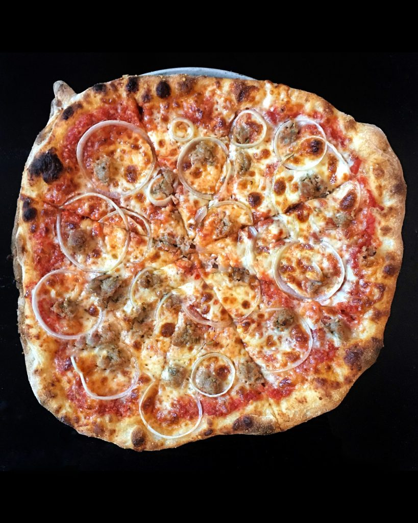 a round pizza with sausage and onions