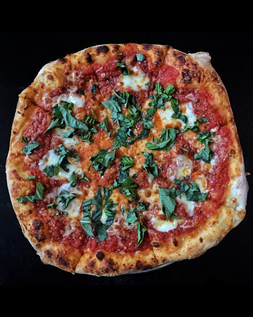a whole pizza pie with basil on it