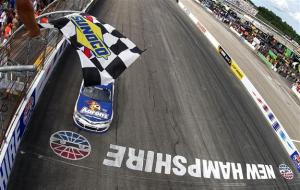 Brian Vickers, driver of the #55 Aaron's Dream Machine Toyota, takes the checkered flag as he crosses the finish line to win the NASCAR Sprint Cup Series Camping World RV Sales 301 at New Hampshire Motor Speedway on July 14, 2013  Photo - Jonathan Ferrey/Getty Images