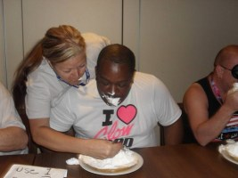 Debbie Dallas feeding GLOW Encyclopedia Sylvester Boyler during the pie eating contest.