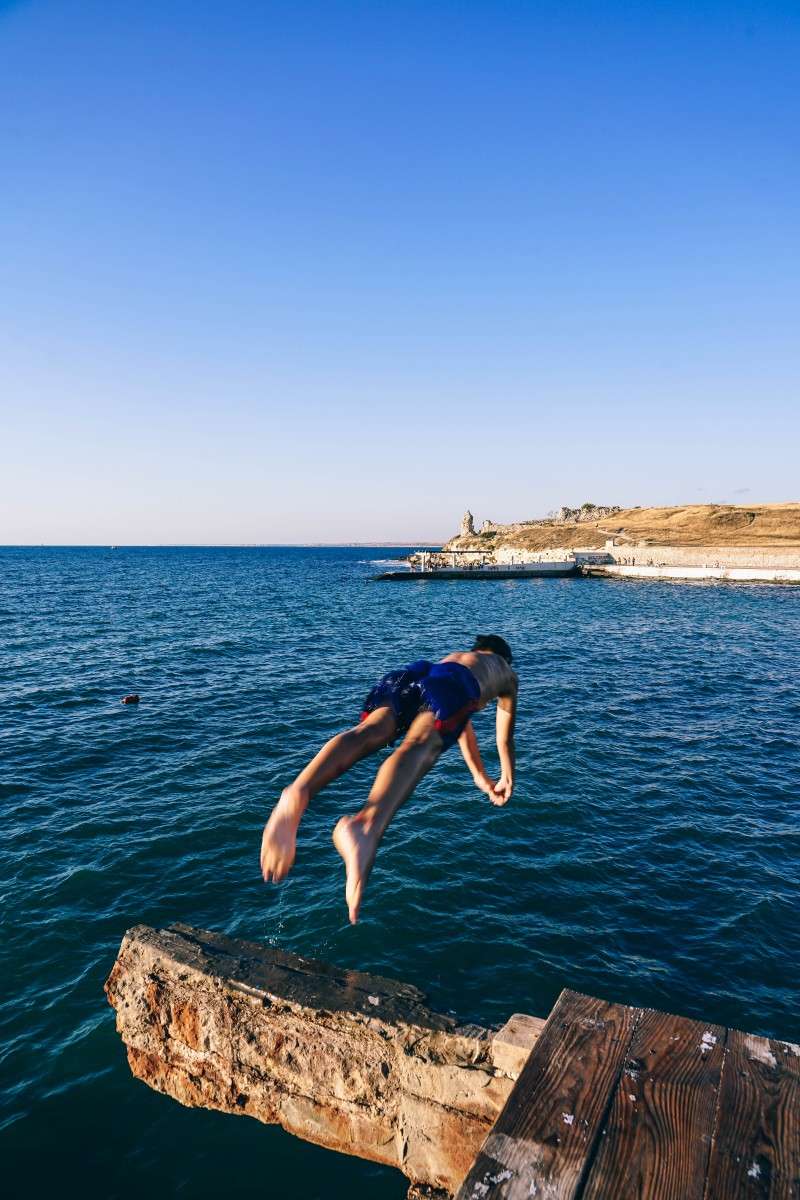 Young boy Jumping into the blue sea nearby sea beach in vacation.