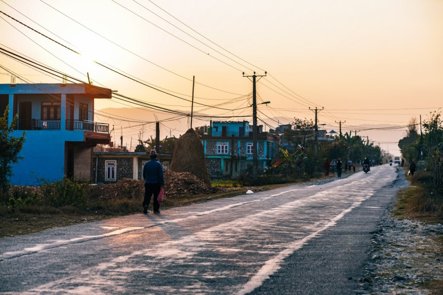 Man walking down Shishuwa road during sunset.