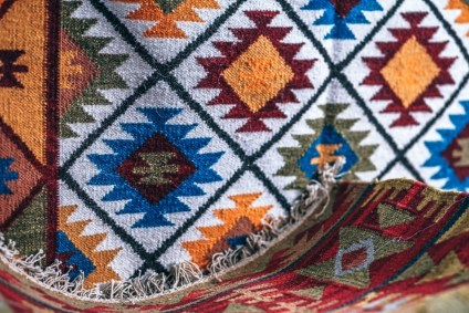 Red-and-Golden-Traditional-Indian-Rug-with-another-Vibrant-Rug-in-the-Background