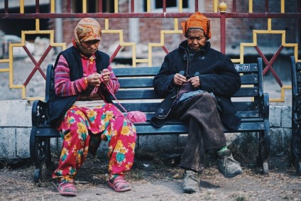 Two-Older-Women-Sitting-on-a-Bench-and-Weaving