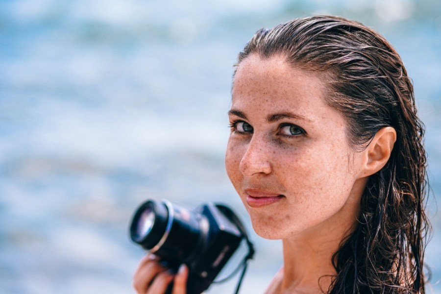 Close-up-Shot-of-a-Beautiful-Freckled-Girl-Holding-a-Camera